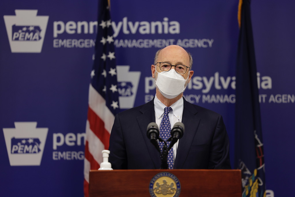 Governor at podium in front of flags with mask