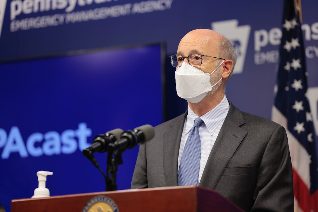 Governor speaking at podium with mask